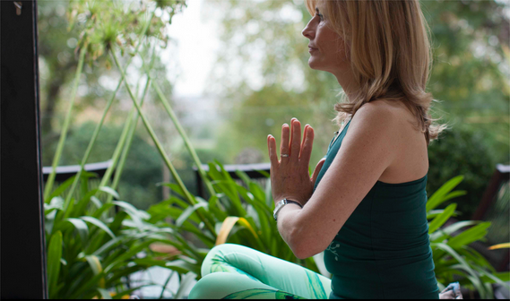 Child Psychotherapist Jane O'Rourke holding a yoga position whilst standing in a tranquil setting with trees and lushious green plants
